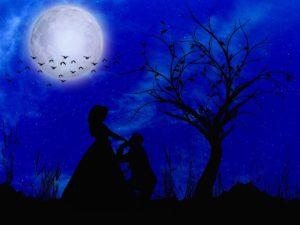 парень целует руку избраннице на фоне луны