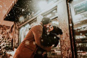 парень обнимает девушку, идет снег