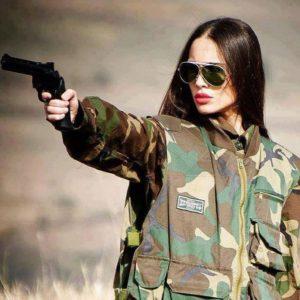 девушка в очках метится из пистолета